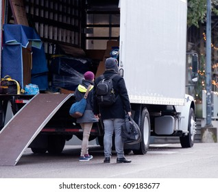 A young couple is transporting goods in a white truck with a boxing trailer and a wheelbarrow ramp to a new place of residence in urban city. The girl and the guy keep the bags in their hands