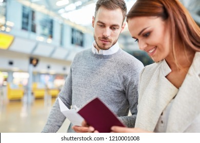 Young couple with travel documents in airport terminal on the way to vacation
