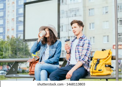 Young couple traveler with backpcaks thinks about route whole drinks coffee at bus stop at city outdoor. Student couple waiting tram.