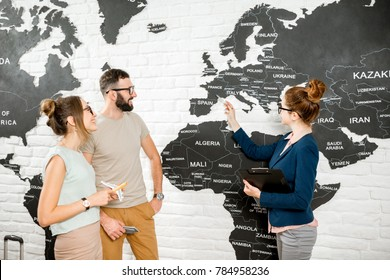 Young couple of travelers choosing a summer trip with travel agent pointing on the world map