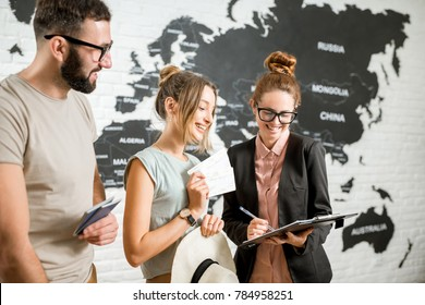 Young couple of travelers choosing a summer strip standing with travel agent on the world map background