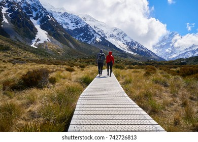 Young couple of travelers hiking on Hooker Valley Track in New Zealand.