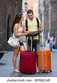 Young couple travelers with luggage and a city map in hands