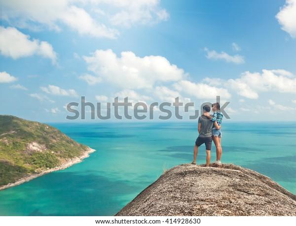 Jeune couple de voyageurs sur une colline offrant une vue imprenable sur l'océan