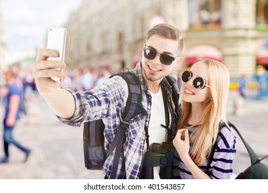Young couple of travelers taking selfie on the street, outdoors