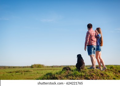A young couple travels in plaid shirts and shorts and the dog standing on the grass back and admire the scenery. Tourists rest on the hill opposite the grass field staring at the horizon.