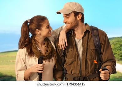 Junge Paare wandern auf dem Land und lächeln einander an.