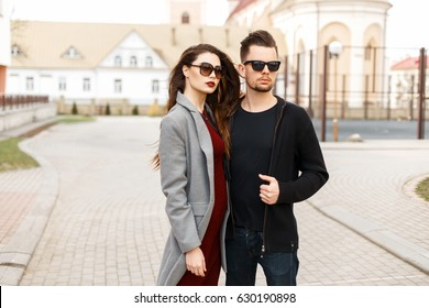 Young couple in trendy sunglasses outdoors.