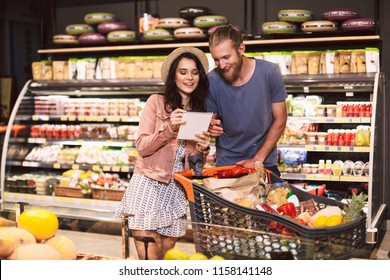 Young couple with trolley full of products reading shopping list spending time together in modern supermarket