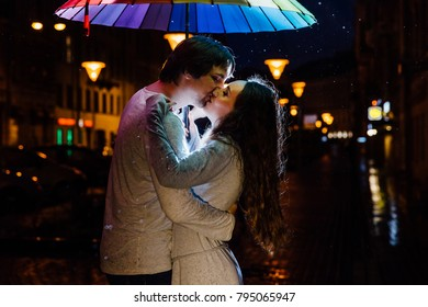 young couple under an umbrella kisses at night on a city street. Lovers on a rainy date under a rainbow umbrella. Valentine's Day.