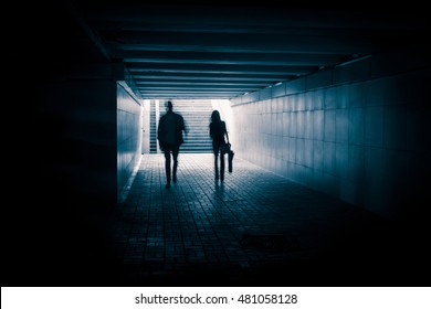 Young couple in the underground dark tunnel.