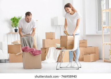 Young couple unpacking moving boxes at new home