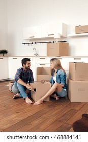 Young couple unpacking in new home and looking at each other