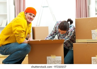 Young couple unpacking in new house