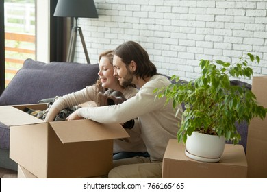 Young couple unpacking open cardboard boxes sitting on sofa in living room, happy new homeowners packing stuff moving out, smiling man and woman settle in new home, move and relocation concept
