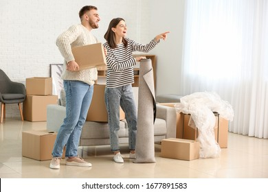 Young couple unpacking things in their new flat on moving day