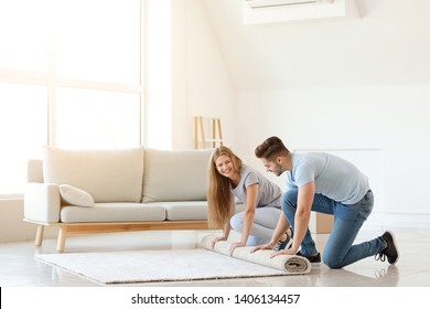 Young couple unrolling carpet on floor