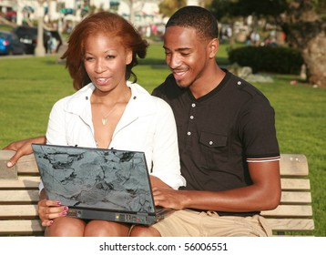 a young couple use a laptop computer outside in a park