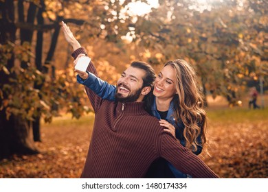 Young couple using cellphone in autumn colored park.