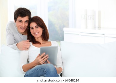 Young couple using electronic tab on sofa