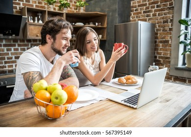 Young couple using laptop while having breakfast at kitchen table