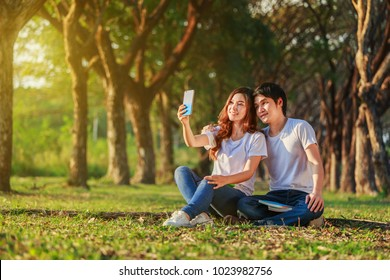 young couple using mobile phone taking a selfie in the park
