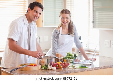 Young couple using notebook to look up recipe