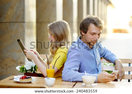 Young couple using smart phone and tablet pc in the outdoor cafe