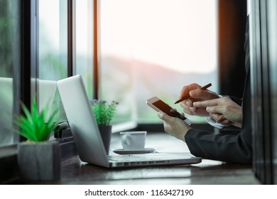 Young couple using smartphone with laptop notebook together in coffee shop with copy space on grass. Information technology gadget or casual business concept