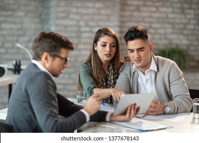 Young couple using touchpad with insurance agent and while making loan repayment plan during a meeting.