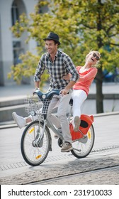 young couple in vacation having fun on a rental bike in the city, in summer