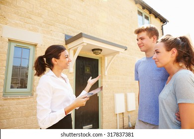 Young couple viewing a house with female real estate agent