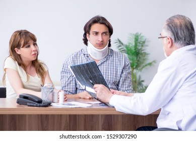 Young couple visiting old male doctor