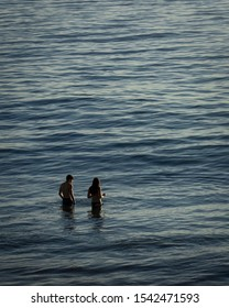 A young couple wades through the calm water of the Pacific Ocean at Hermosa Beach, California during sunset