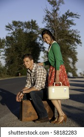Young couple waiting for a ride along the roadside with vintage travel bags