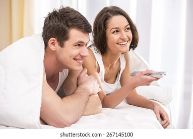 Young couple waking up and watching TV on the bed at home.