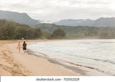 Young couple walking along Hanalei Bay beach on the island Kauai, Hawai
