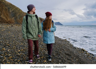 young couple walking along the shore of the stormy sea