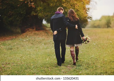 young couple walking away, autumn day