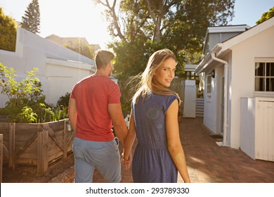 Young couple walking in the backyard holding hand in hand on a bright summer day, with woman looking back over shoulder at camera.