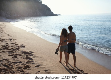 Young couple walking by the beach