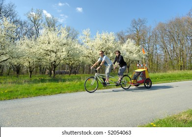 a young couple walking, cycling tandem