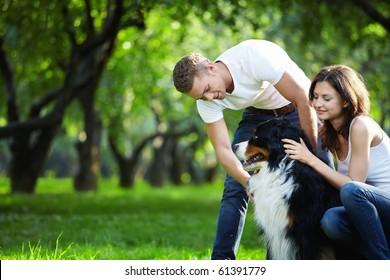 A young couple walking a dog in the park