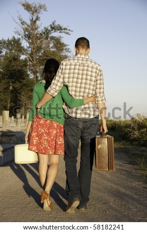Young couple walking down path with their vintage suitcase in hand.They have arm around each other.