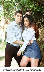young couple walking in the forest, posing near tree, summer nature, bright sunlight, shadows and green leaves, romantic feelings