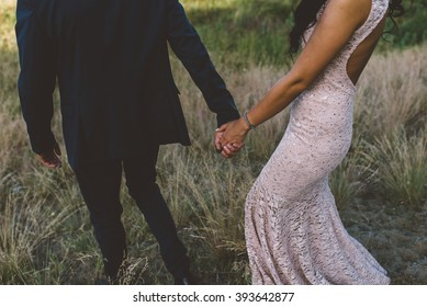 Young couple walking and holding hands outdoors.