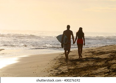 Young couple walking on the beach goes to surf