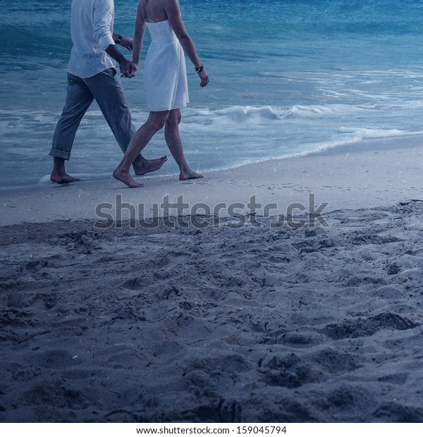 Young couple walking on the beach in the moonlight