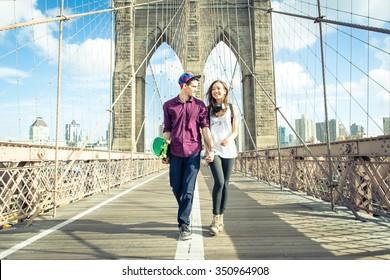 Young couple walking on the brooklyn bridge
