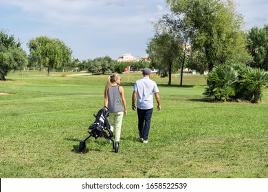 Young couple walking on a golf course with a cart to transport the equipment with buildings and trees in the background